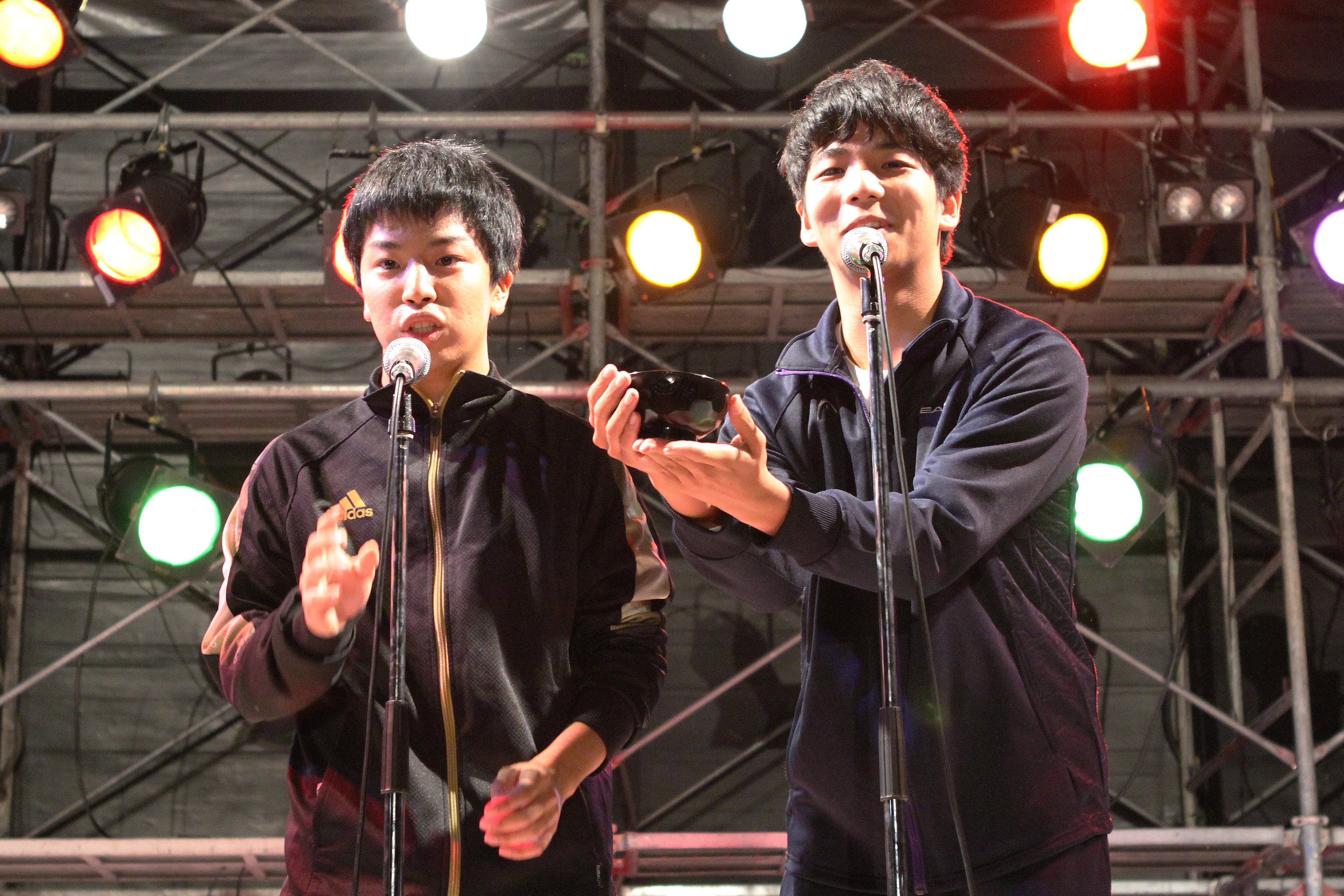 おわんを手に漫才を披露する宮崎喬至さん(右)と武田諒さん(ステージ奏で 撮影=児玉七海)